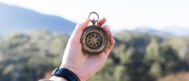 Person holding compass outdoors.