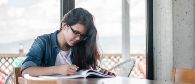 Girl studying at kitchen table.