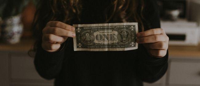 Girl holding dollar bill.