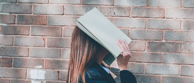 Girl holding book over face.