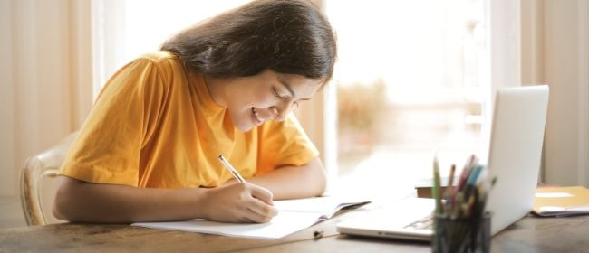 Girl studying and taking notes.